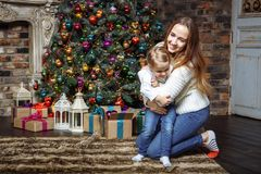 Young mother playing with her little daughter near the Christmas tree. stock photos