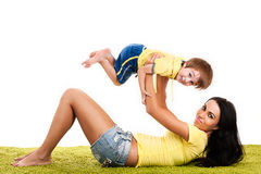 Young mother playing with her son on a green grass Royalty Free Stock Image