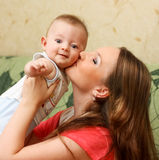 Young mother playing with her son at home. Royalty Free Stock Image