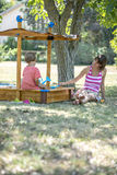 Young mother playing with her toddler son sitting in a sandbox. Under a tree on a sunny summer day Stock Photos