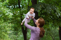 Young mother playing with a laughing baby girl in a park. Young happy mother playing with a laughing baby girl in a park royalty free stock image
