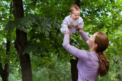 Young mother playing with a laughing baby girl in a park. Young happy mother playing with a laughing baby girl in a park Royalty Free Stock Photos