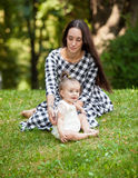 Young mother playing with little baby daughter at park Stock Image