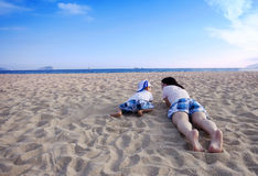 Young mother playing with son on the beach Stock Photos