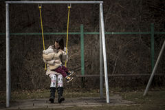 Young mother playing on a swing with her child