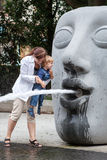 Young mother playing with toddler boy with water of fountain Stock Image