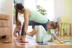 Young mother playing twister with her daughters. Happy family have a fun time in holiday Stock Photo