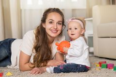 A young mother plays with a baby. Royalty Free Stock Photography
