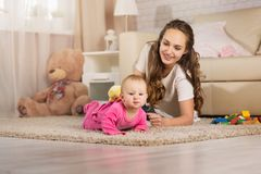 A young mother plays with a baby. Royalty Free Stock Photo
