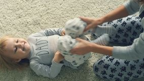 Young mother plays with daughter on the floor stock video