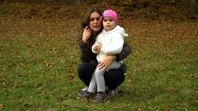 A young mother plays with her little daughter in the autumn forest. Mom and daughter communicate. They are happy. stock footage