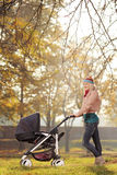 A young mother posing with a baby stroller in autumn Stock Photo