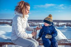 Young mother pours a mug of tea from thermos. Little boy child looks at the mug. In winter, in the city on a bench in a. Young mother pours a mug of tea from a royalty free stock photos
