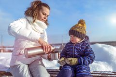 Young mother pours a mug of tea from thermos. Little boy child looks at the mug. In winter, in the city on a bench in a. Young mother pours a mug of tea from a stock photography