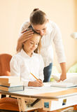 Young mother praising daughter doing homework at desk Stock Image