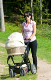 Young mother with pram. Smiling young woman pushing pram or baby carriage in countryside Royalty Free Stock Photography