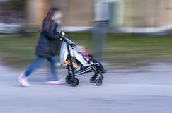 Young mother with pram. In blurred motion Stock Image