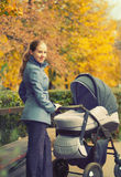 Young mother with pram on walk in autumn Stock Photo