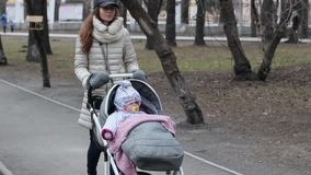 Young mother with pram walking in the spring park. Love and Family Concept.  stock video footage