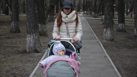 Young mother with pram walking in the spring park. Love and Family Concept.  stock footage