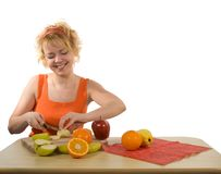 Young mother preparing fruit salad. Young blond, happy and healthy looking woman preparing fruit salad (isolated, with copy space stock photos