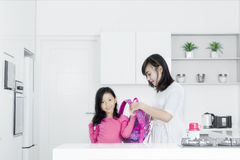 Young mother preparing girl for school Stock Photos