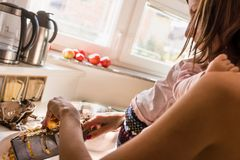 Young mother preparing a meal in the kitchen Royalty Free Stock Images