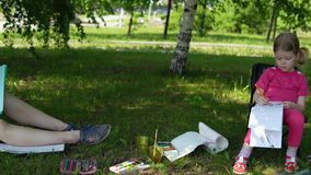 Mom and daughter are engaged in creativity in the park in the shade under the trees. A young mother and a pretty blonde daughter are engaged in creativity in a stock video
