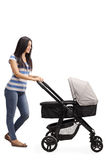 Young mother pushing a baby stroller Stock Photos