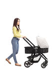 Young mother pushing a baby stroller Royalty Free Stock Photography