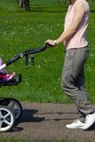 young mother pushing buggy royalty free stock photo
