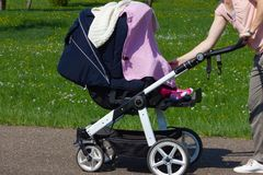 young mother pushing buggy stock image
