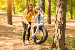 Young mother pushing child daughter on tire swing in park