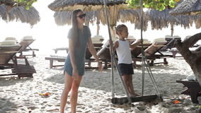 Young mother pushing cute little daughter on swing at the sandy beach. With sunbeds on the background stock video footage