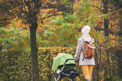 Young mother pushing stroller in autumn park Royalty Free Stock Image