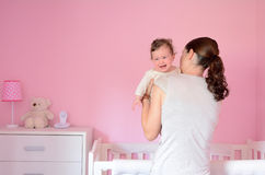 Young mother puts her baby to sleep Stock Photo