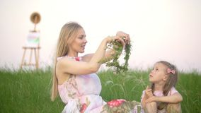 Young mother puts on wreath on her head and little daughter sitting on the summer meadow recreation outdoors stock footage