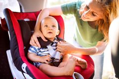 Young mother putting baby boy in the car seat. Stock Photos