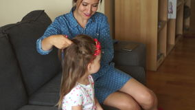 Young mother putting daughters hair in pigtails. A happy family. Mothers Day. Women`s Day. stock video footage