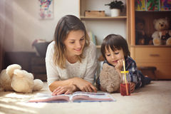 Young mother, read a book to her tho children, boys, in the livi Royalty Free Stock Images