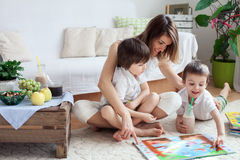 Young mother, read a book to her tho children, boys, in the living room stock images