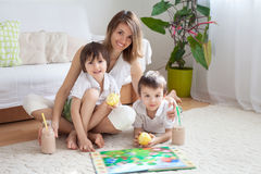 Young mother, read a book to her tho children, boys, in the livi Royalty Free Stock Photo