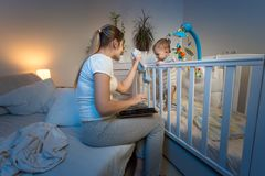 Beautiful young mother reading book aand giving toy to her baby son standing in cot at night. Young mother reading book aand giving toy to her baby son standing royalty free stock photography