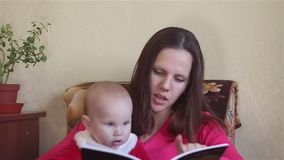 Young mother reading a book with baby stock footage