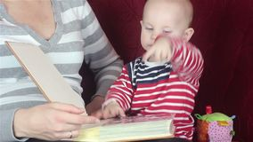 Young mother reading a book with baby stock video footage