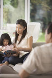 Young Mother Reading Book With Daughter On Sofa Stock Photo
