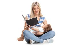 Young mother reading a book with her baby boy sleeping in her la. P isolated on white background Royalty Free Stock Photos