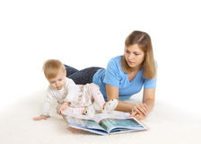 Young mother reading book with her little daughter. On the floor Royalty Free Stock Photos