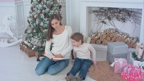 Young mother reading book to distract her son from Christmas presents Royalty Free Stock Photography