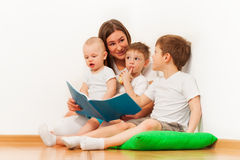 Young mother reading book to her age-diverse kids stock images